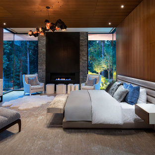 Diseño de dormitorio principal, actual, extra grande, con marco de chimenea de metal, paredes marrones y chimenea lineal