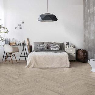 Esempio di una grande camera da letto stile loft design con pareti bianche, pavimento in gres porcellanato e pavimento grigio