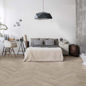 Contemporary bedroom with light herringbone wood look porcelain floors
