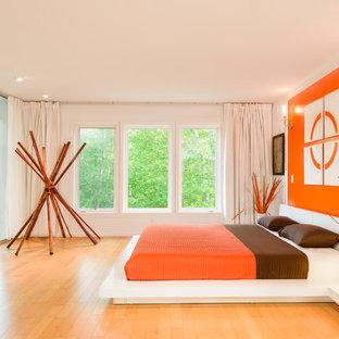 Foto på ett funkis sovrum, med vita väggar, mellanmörkt trägolv och orange golv