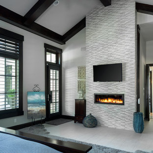 Photo of a large contemporary master bedroom in Kansas City with grey walls, a two-sided fireplace, a stone fireplace surround and porcelain floors.
