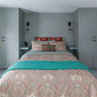 На фото: гостевая спальня среднего размера в современном стиле с зелеными стенами, деревянным полом и серым полом с