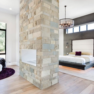 Inspiration for a contemporary master bedroom in Salt Lake City with grey walls, medium hardwood floors, a two-sided fireplace, a stone fireplace surround and brown floor.