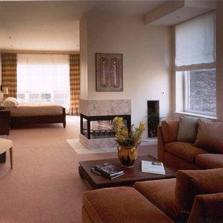 Idee per una grande camera matrimoniale minimal con pareti beige, moquette, camino bifacciale e cornice del camino piastrellata