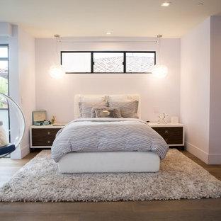 Imagen de dormitorio actual, grande, con paredes púrpuras, suelo de madera en tonos medios y suelo marrón