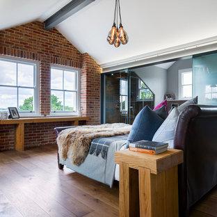 ロンドンの広いインダストリアルスタイルのおしゃれな主寝室 (無垢フローリング、赤い壁、茶色い床) のレイアウト