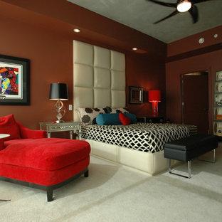 Immagine di una grande camera matrimoniale design con pareti arancioni e moquette