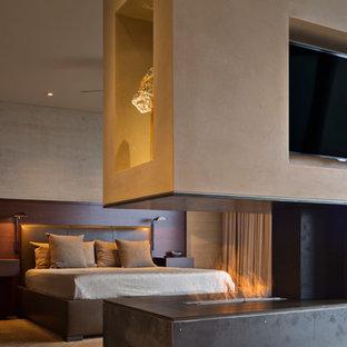 Foto de dormitorio principal, moderno, extra grande, con paredes beige, suelo de madera en tonos medios, chimenea de doble cara y marco de chimenea de metal