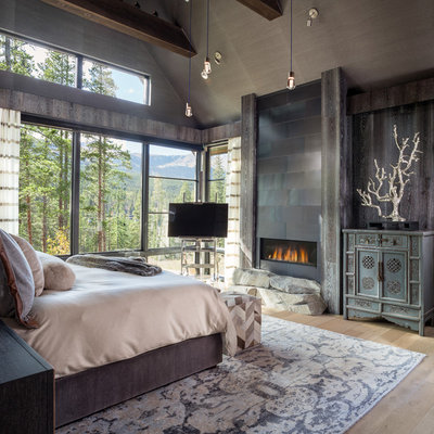 Example of a mountain style master light wood floor and beige floor bedroom design in Denver with a ribbon fireplace