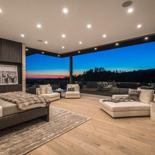 Diseño de dormitorio principal, actual, extra grande, con paredes marrones, suelo de madera clara, marco de chimenea de piedra, chimenea lineal y suelo beige
