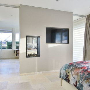 This is an example of a contemporary master bedroom in Amsterdam with beige walls, limestone floors and a two-sided fireplace.