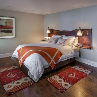 Diseño de dormitorio principal, rural, de tamaño medio, sin chimenea, con paredes grises, suelo de madera en tonos medios y suelo marrón