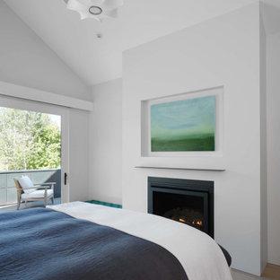 Bild på ett mellanstort funkis huvudsovrum, med vita väggar, ljust trägolv, en standard öppen spis, en spiselkrans i gips och brunt golv