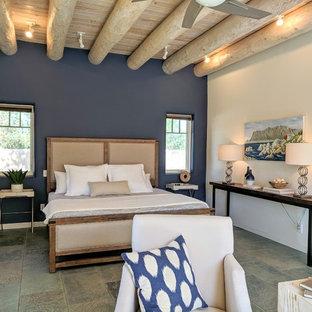 Modelo de dormitorio principal, de estilo americano, de tamaño medio, con paredes blancas, suelo de pizarra, chimenea de esquina, marco de chimenea de yeso y suelo gris