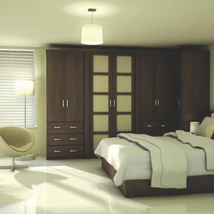 Inspiration for a large contemporary master bedroom in Hampshire with beige walls and marble floors.