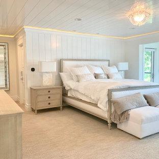 Идея дизайна: большая хозяйская спальня в современном стиле с белыми стенами, ковровым покрытием, стандартным камином, фасадом камина из каменной кладки, бежевым полом и потолком из вагонки