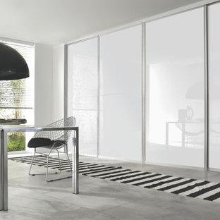 На фото: большая хозяйская спальня в современном стиле с белыми стенами и полом из известняка с