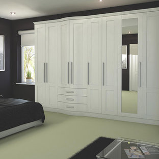 This is an example of a large contemporary master bedroom in Hampshire with black walls and carpet.