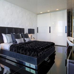 Modelo de dormitorio moderno, sin chimenea, con paredes blancas, suelo de baldosas de cerámica y suelo negro