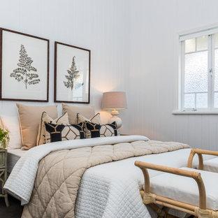 Immagine di una camera da letto costiera con pareti bianche, moquette, pavimento nero e pareti in perlinato
