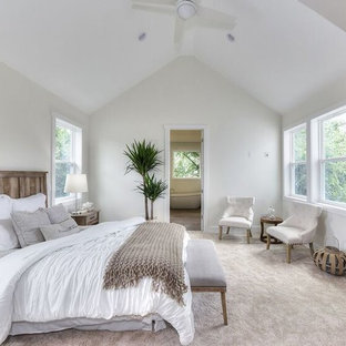 Example of a large beach style master carpeted and beige floor bedroom design in Jacksonville with white walls and no fireplace