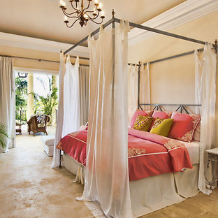 Design ideas for a mid-sized mediterranean master bedroom in Other with beige walls, travertine floors, no fireplace and brown floor.