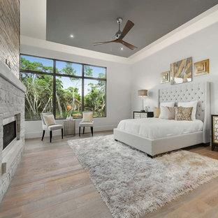 Modelo de dormitorio principal, actual, extra grande, con paredes grises, suelo de madera clara, chimenea tradicional, marco de chimenea de piedra y suelo gris