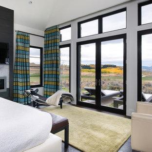 Imagen de dormitorio principal, actual, de tamaño medio, con paredes blancas, suelo de madera oscura, marco de chimenea de hormigón y chimenea lineal