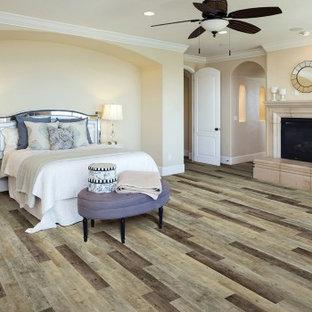 Foto de dormitorio principal, contemporáneo, grande, con suelo vinílico, paredes beige, chimenea tradicional, marco de chimenea de hormigón y suelo multicolor