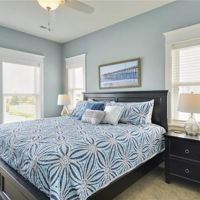 Example of a mid-sized beach style guest carpeted bedroom design in Other with blue walls and no fireplace