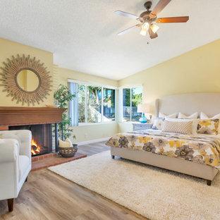 ロサンゼルスのトランジショナルスタイルのおしゃれな寝室 (黄色い壁、無垢フローリング、標準型暖炉、茶色い床、三角天井) のインテリア