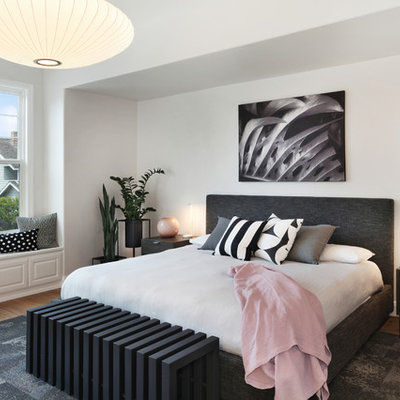 Example of a large trendy master medium tone wood floor and brown floor bedroom design in Orange County with white walls