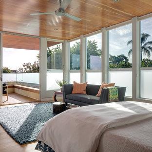 Ejemplo de dormitorio principal y madera, tropical, grande, con paredes multicolor, suelo de madera clara, chimenea de esquina, marco de chimenea de piedra y suelo marrón