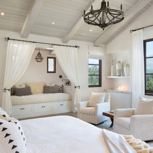 Design ideas for a large mediterranean master bedroom in Santa Barbara with white walls, light hardwood floors, a ribbon fireplace and brown floor.