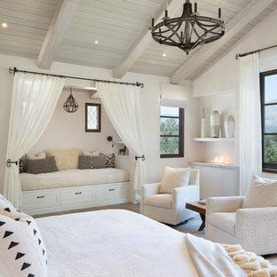 Foto på ett stort medelhavsstil huvudsovrum, med vita väggar, ljust trägolv, en bred öppen spis och brunt golv