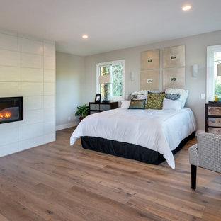 Modelo de dormitorio principal, minimalista, grande, con paredes grises, suelo de madera clara, chimenea tradicional, marco de chimenea de baldosas y/o azulejos y suelo gris
