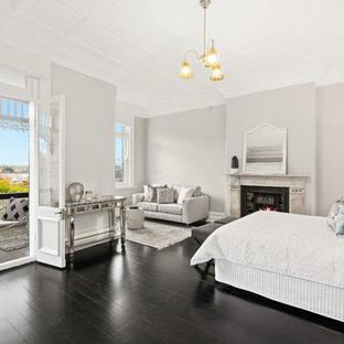 Ejemplo de dormitorio principal, tradicional renovado, de tamaño medio, con paredes grises, chimenea tradicional, marco de chimenea de piedra, suelo negro y suelo de madera pintada