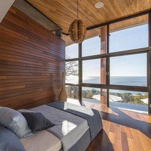 Immagine di una piccola camera degli ospiti contemporanea con pavimento in legno massello medio, nessun camino e pareti beige
