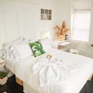 Ispirazione per una camera matrimoniale tropicale di medie dimensioni con pareti bianche, pavimento in legno verniciato e pavimento nero