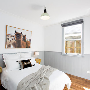 This is an example of a scandinavian bedroom in Other with white walls, medium hardwood floors and brown floor.