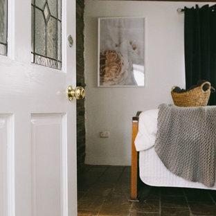 Foto de dormitorio campestre, pequeño, con paredes blancas, suelo de pizarra y estufa de leña