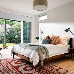 Inspiration för mellanstora 50 tals sovrum, med vita väggar och ljust trägolv