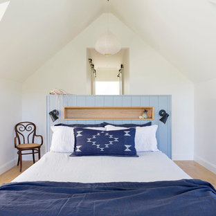 Photo of a small country guest bedroom in Wollongong with white walls, light hardwood floors and brown floor.