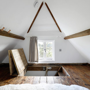 Bedroom - small country loft-style dark wood floor bedroom idea in Sussex with white walls