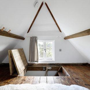 Immagine di una piccola camera da letto stile loft country con pareti bianche e parquet scuro