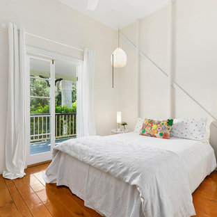 Inspiration for a country bedroom in Brisbane with white walls, medium hardwood floors and brown floor.