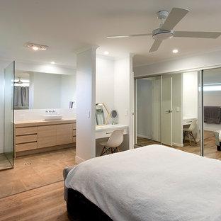 Modelo de dormitorio principal, minimalista, de tamaño medio, con paredes blancas, suelo vinílico y suelo marrón