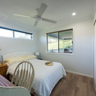 Modelo de habitación de invitados romántica, de tamaño medio, con paredes blancas, suelo vinílico y suelo marrón