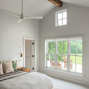 Modelo de dormitorio abovedado, de estilo de casa de campo, con paredes blancas, suelo de madera pintada y suelo blanco