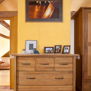 Inspiration pour une grande chambre parentale rustique avec un mur jaune et un sol en bois clair.